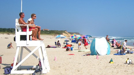 Lifeguards watch over a beach while people enjoy the sun and sand with colorful umbrellas.