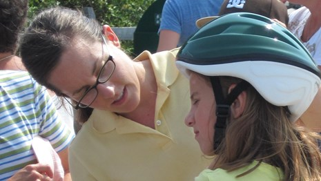 A young park visitor tries on a bike helmet while a volunteer helps her adjust it.