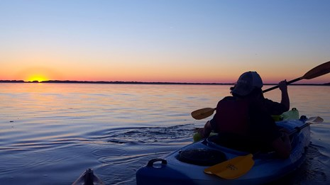 S person in a kayak on calm waters faces the setting sun.