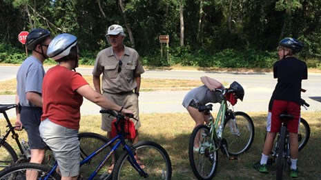 A man in a khaki park service volunteer shirt talks to bicyclists wearing helmets on a paved trail.