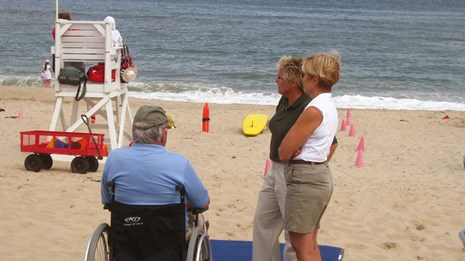 A man sits in a wheelchair at the end of a blue woven mat on a sandy beach talking to two women.