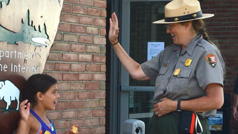 A ranger swears in two children as Junior Rangers outdoors in front of a large arrowhead logo.