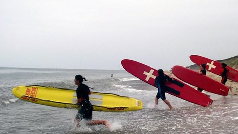 Junior Lifeguards run into surf on a beach carrying large red and yellow surfboards.