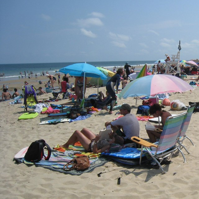 Beach goers enjoy the sun and surf with blankets and colorful umbrellas.