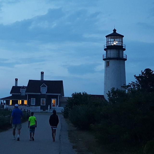 Three people walk up to a lighthouse with the tower light lit at dusk.