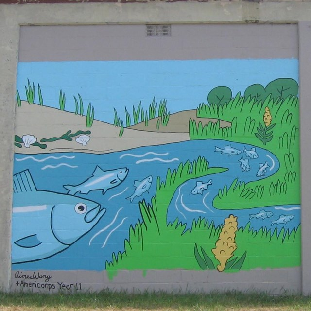 Two side-by-side painted murals on the side of a cinder block building depict o river scene.