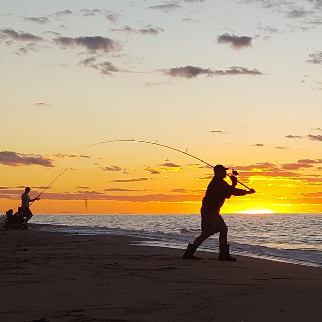 The silhouettes of fishermen are framed against a brilliant sunset.