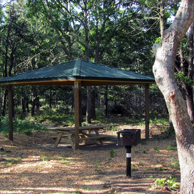 A picnic bench and barbecue grill sit in front of an open-sided wooden shelter