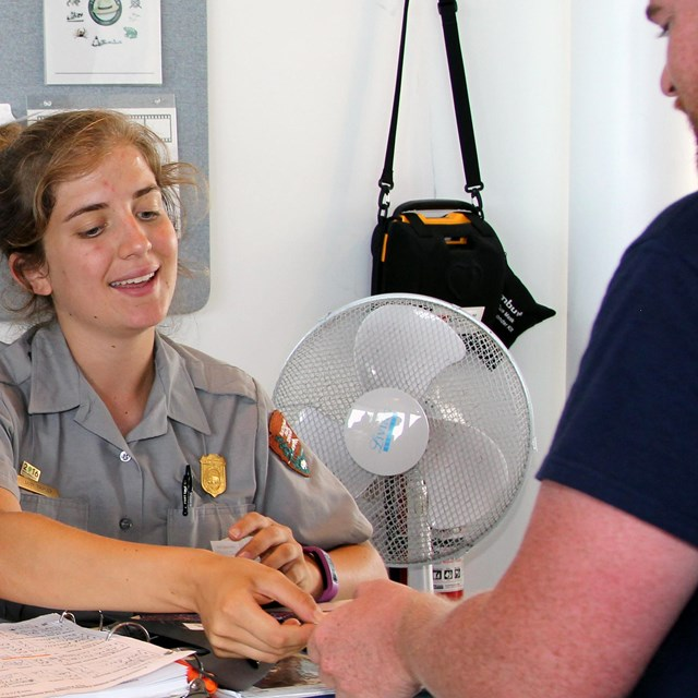 A smiling Ranger assists a visitor at a counter with a wall clock and bulletin board behind her.