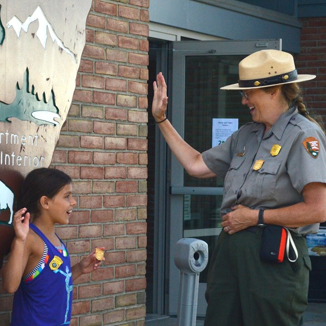 A ranger administers a junior ranger oath to two young park visitors.