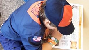 Cub scout in uniform writing in a workbook
