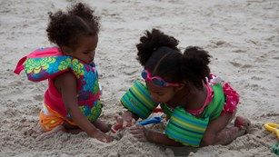 Two young girls playing in the sand.