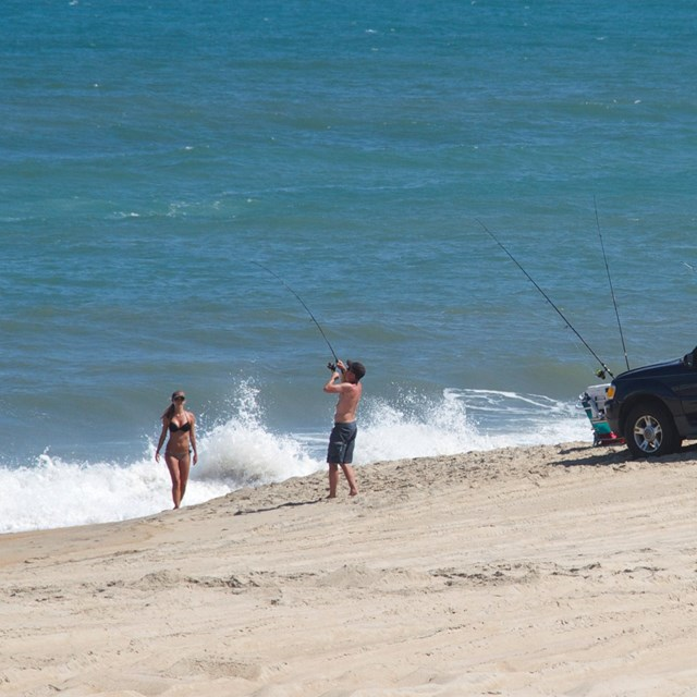 Two ORVs with beachgoers