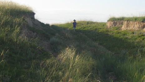 A person walks up a hill through a grassy swale.