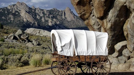 A covered wagon sits in front of a large rock outcropping.