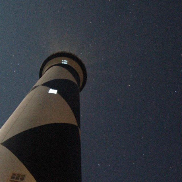 The Cape Lookout Lighthouse against a star-filled sky.