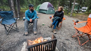 A man and a woman sit in camping chairs next to a campfire