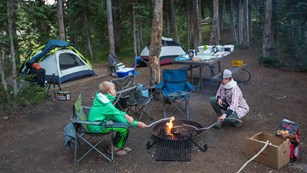 Two people sit around a campfire in a frontcountry campsite