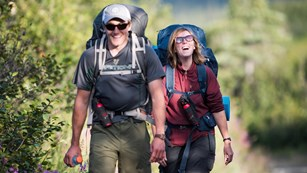 A man and a woman carry backpacks while hiking