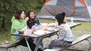 Three women sit at a picnic table eating and laughing. A tent is in the background.