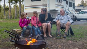 A family sits next to a campfire in a campground