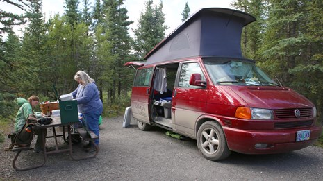 Two people at a picnic table next to a red camper-style van