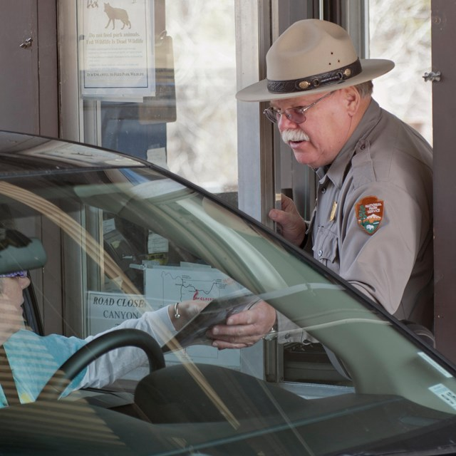 A Park Ranger greets a visitor in a car at the entrance station
