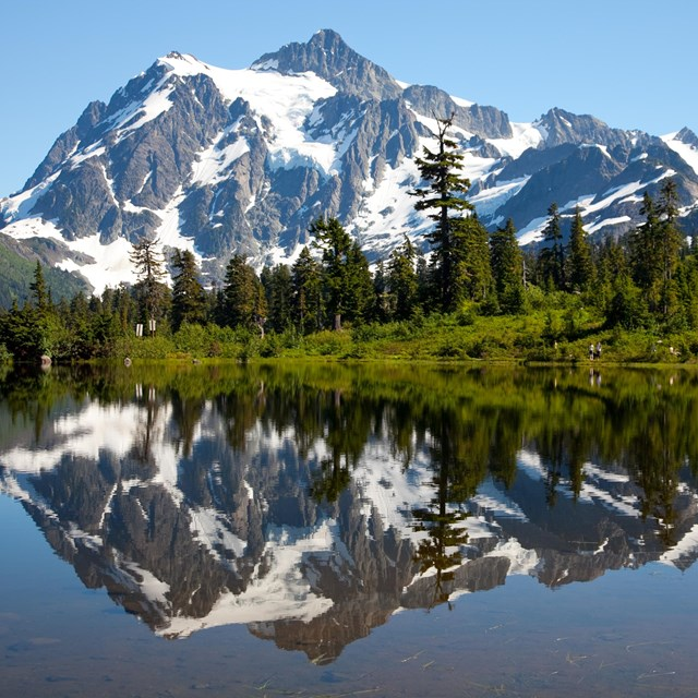 A snowy mountain is reflected in a mountain lake