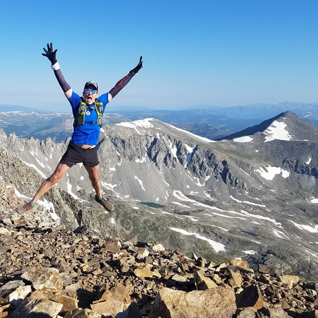 man in running clothes jumps in the air on top of a mountain with snowy peaks in the background