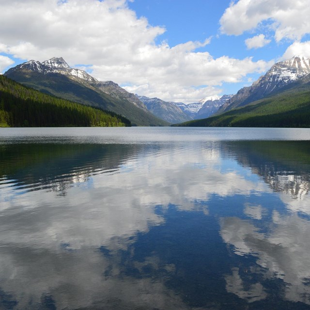 a clear blue lake reflects white clouds with mountains in the background