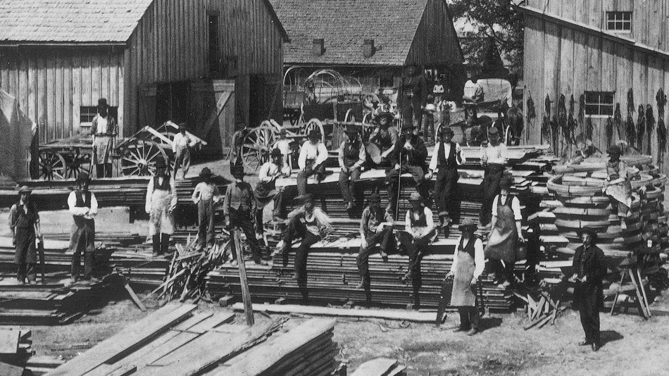 Civil War soldiers pose in the yard of the wagon and harness shops at Camp Nelson