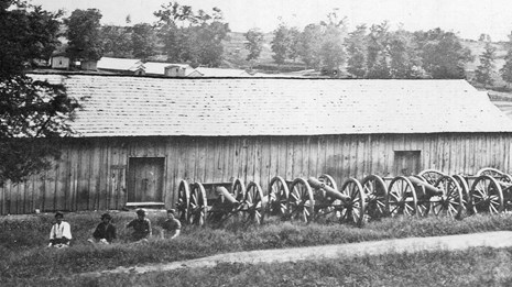 Four soldier sit beside a row of cannons outside a wooden ordnance warehouse