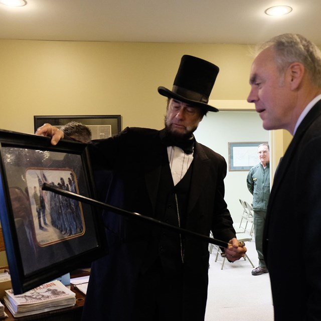 Man dressed as Abe Lincoln uses cane to point out framed artwork being observed by Ryan Zinke