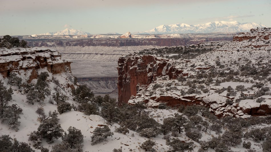 a canyon view with snow on the ground. Mountains rise in the distance.