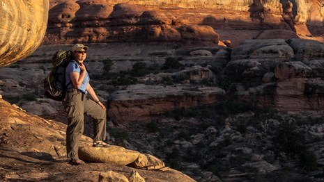 a backpacker stands on a ledge overlooking a canyon