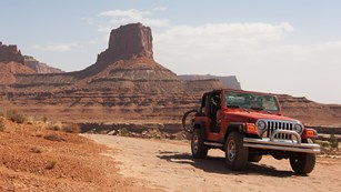 a Jeep driving on a flat, rocky road