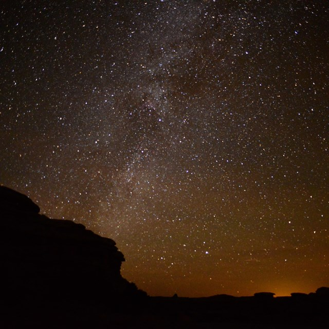 a star-filled sky over silhouetted rock formations