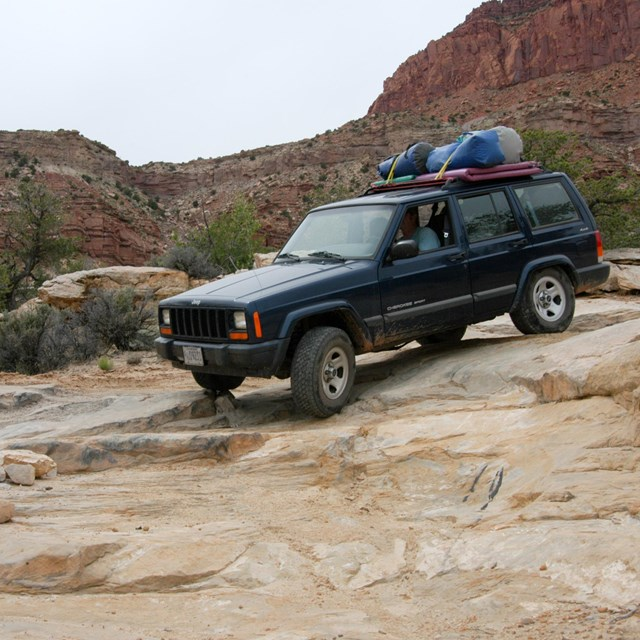 a blue Jeep drives over slickrock