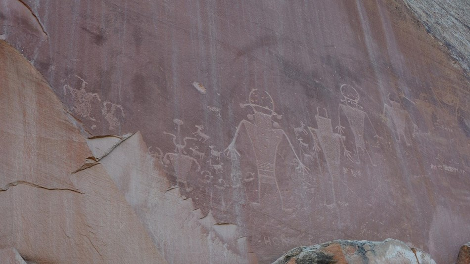 Petroglyphs of human-like figures in red sandstone.
