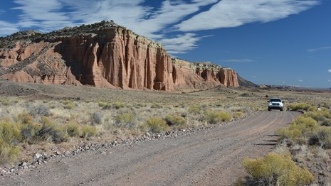 White SUV on gravel road, with red cliffs and blue skies and clouds in the background.
