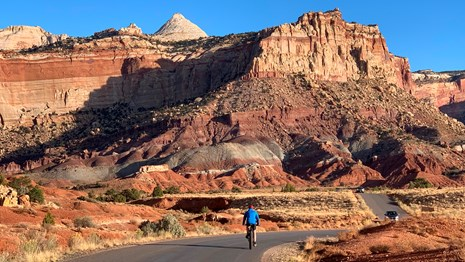Cars and a bicyclist on a road which parallels sandstone cliffs