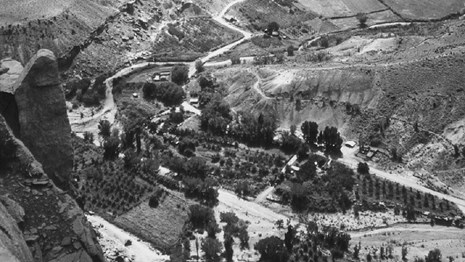 Black and white photo of canyon with orchards, cliffs, and a river.