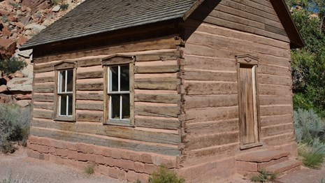 Small log cabin-like building with windows and a door, below red rock cliffs and blue sky.