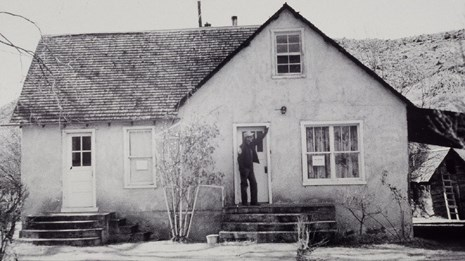 Black and white photo of a man standing on the porch of a house.
