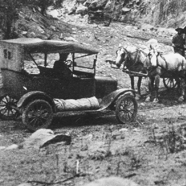 Black and white photo of old fashioned car meeting two wagons pulled by horses in a narrow canyon.