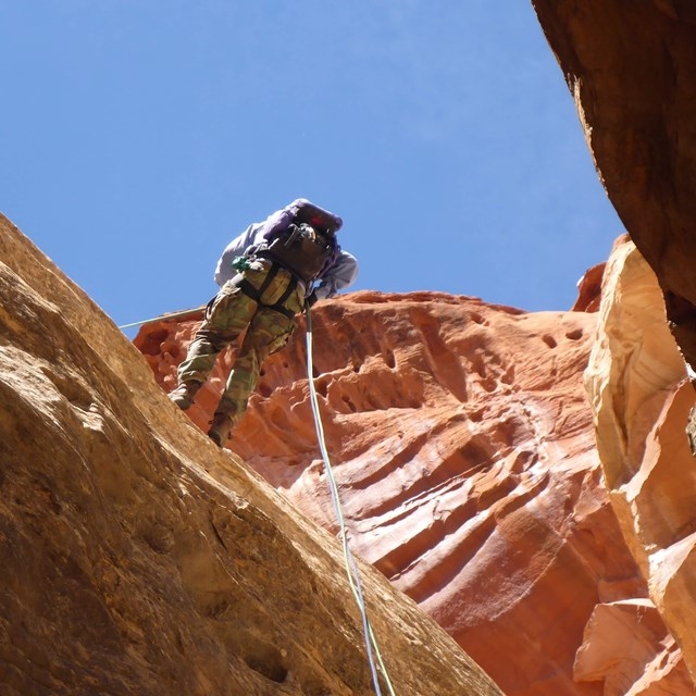 Person rapelling down redrock cliff wall with blue sky above.