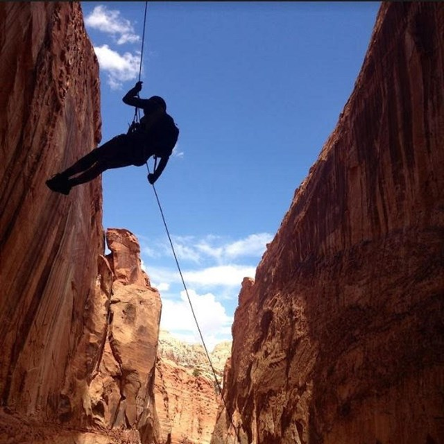 Silhouette of person on rope, between cliffs, with blue sky in the background.