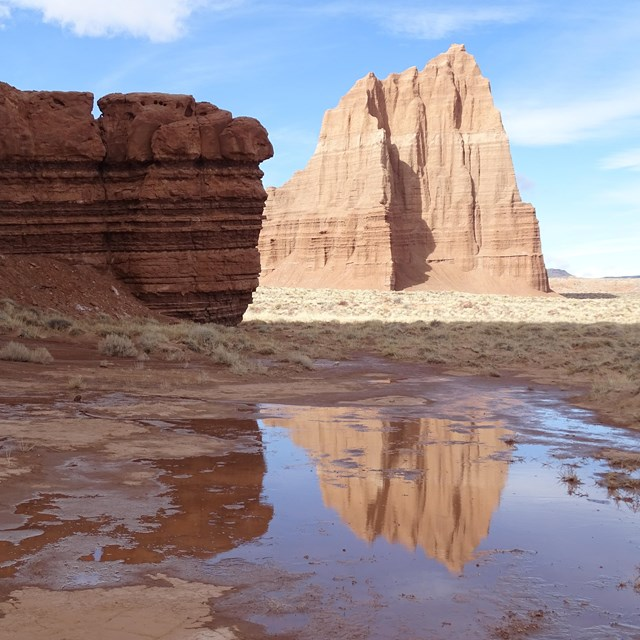 Large red, triangular monolith, reflected in a puddle, with blue sky above, and red rock to the side