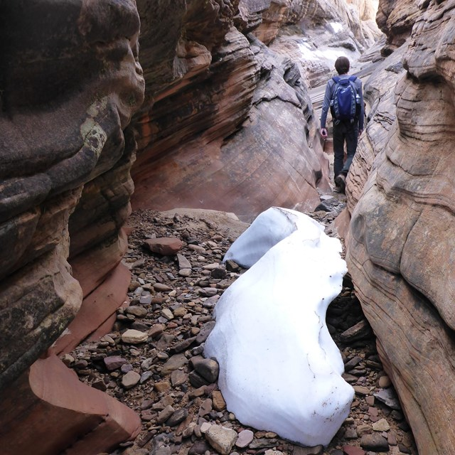 Narrow slot canyon with snow and hiker