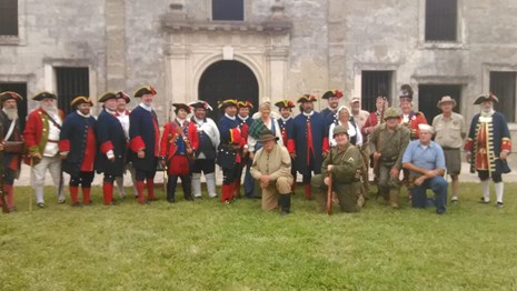 a group photo of reenactors in uniforms from many different time period